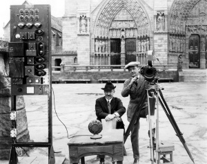 On the left is director Wallace Worsley, and on the right by the camera, cinematographer Robert Newhard. The radio set up was used so Worsley could direct the crowd scenes, in which a couple thousand of extras might be present at any one time.